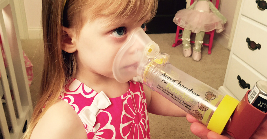 Young asthma patient uses an inhaler.