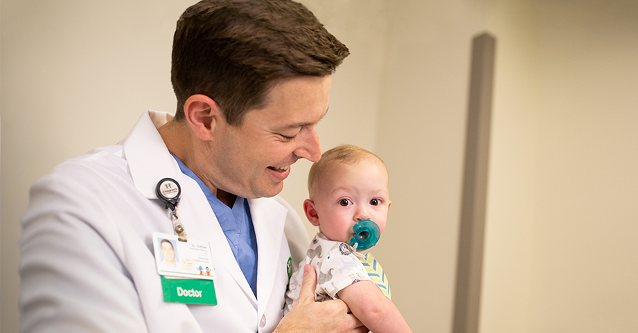 Dr. Clifton holds a baby patient before  surgery.