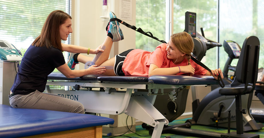 Pediatric sports physical therapist guiding teenage athlete after knee surgery