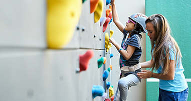 rehab therapist helping patient climb rock wall