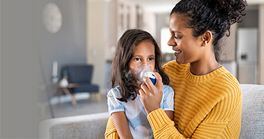 Mom giving daughter breathing treatment for asthma
