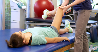 Pediatric physical therapist helping teen patient with hip condition
