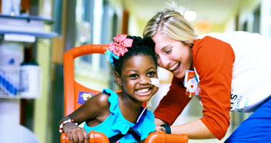 nurse laughing with girl on bike in hospital hallway