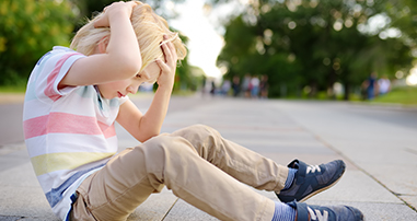 Young boy sitting on sidewalk holding head