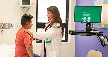 Doctor listening to stethoscope with a young boy at an urgent care