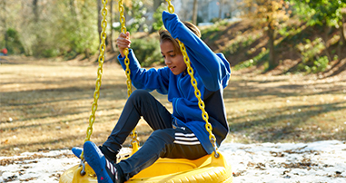 Boy playing on tire swing