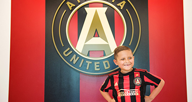 Andrew Jimenez with pediatric cancer smiling in Atlanta United jersey