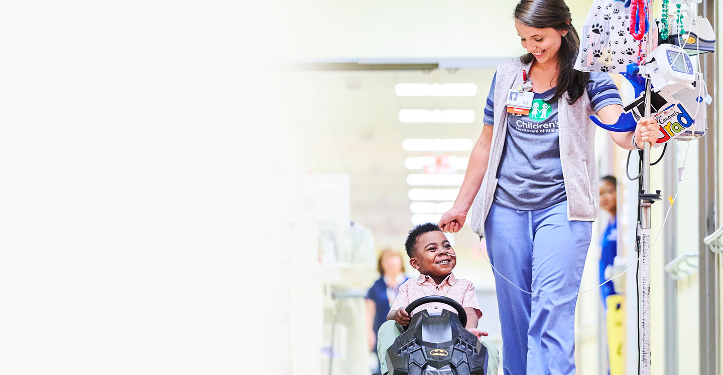 nurse walking pediatric heart patient down the hall