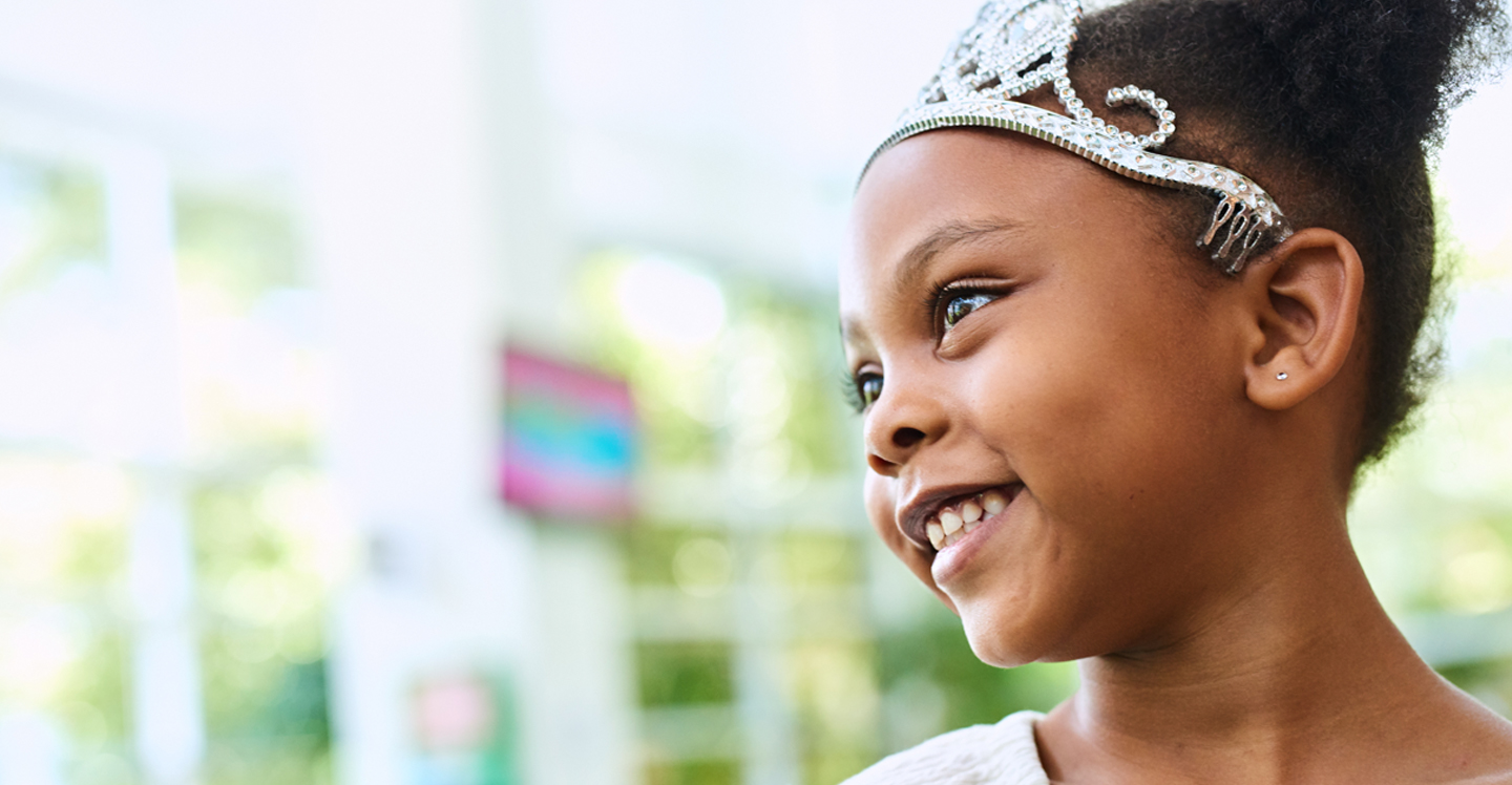 little girl smiling wearing crown in lobby of pediatric hospital