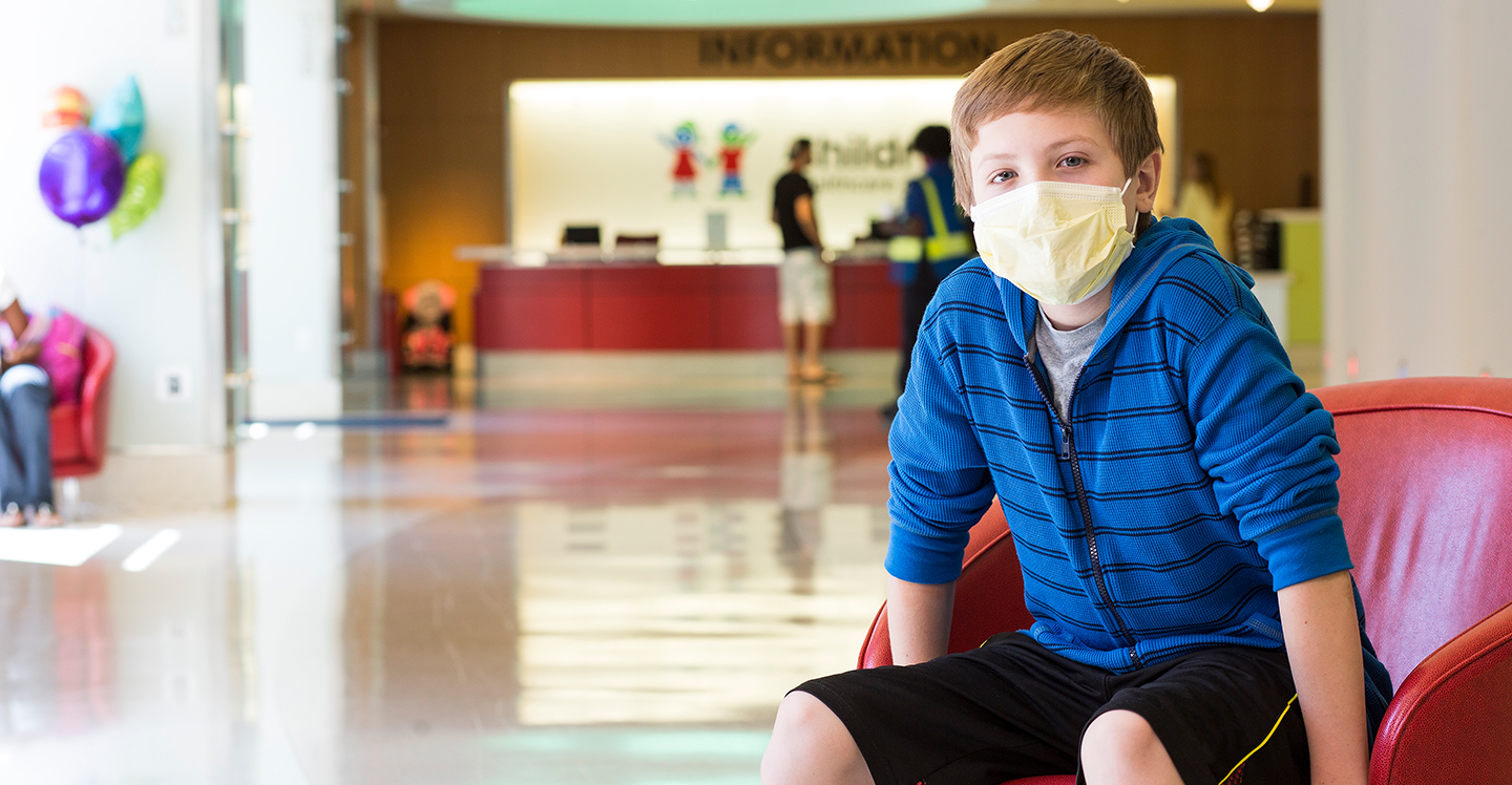 Boy wearing face mask sitting in chair at Egleston hospital