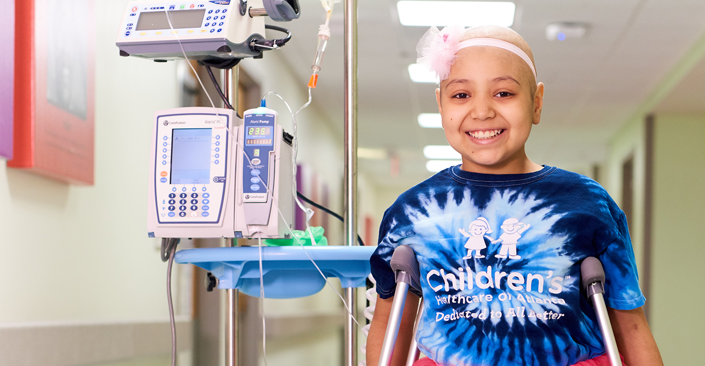 Pediatric cancer patient wearing a tutu smiles in hospital hallway