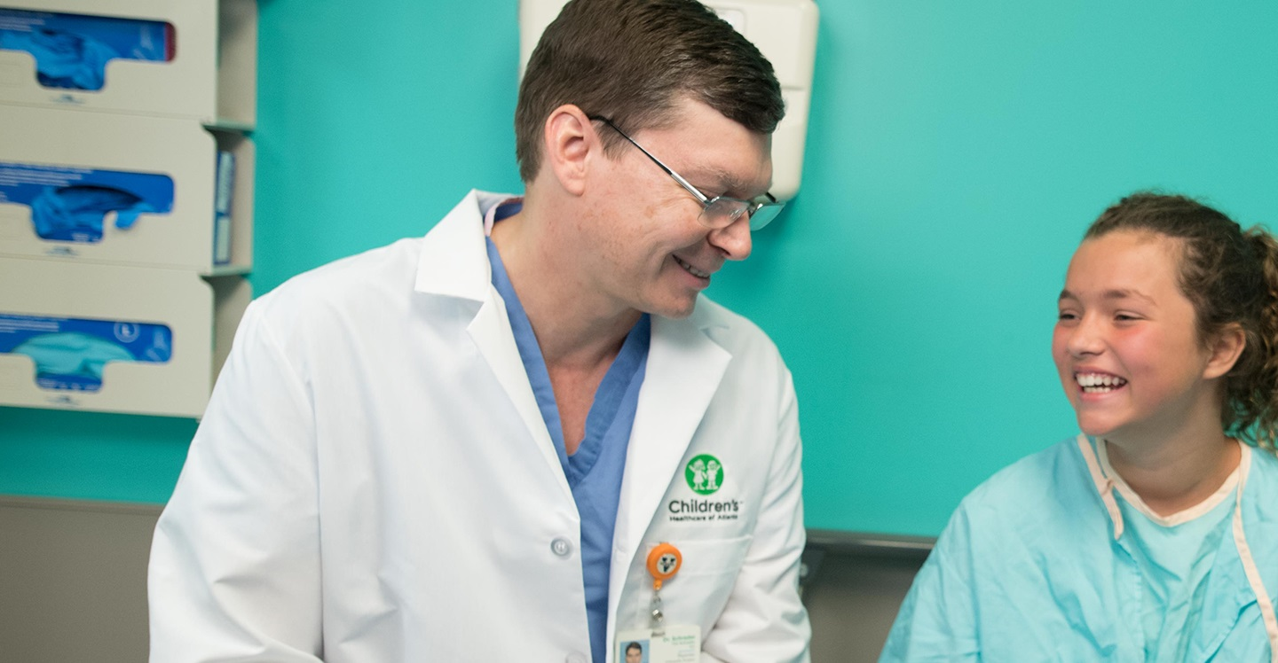 Pediatric orthopedic specialist at Children's Healthcare of Atlanta laughs with a hip patient in clinic