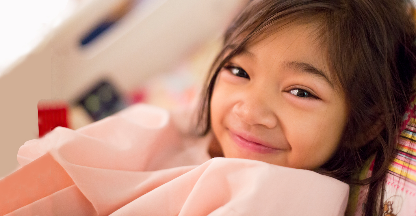 girl smiling in hospital bed