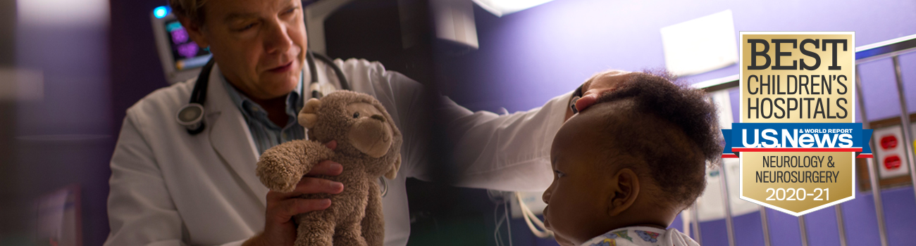 neuro doctor holding bear with baby