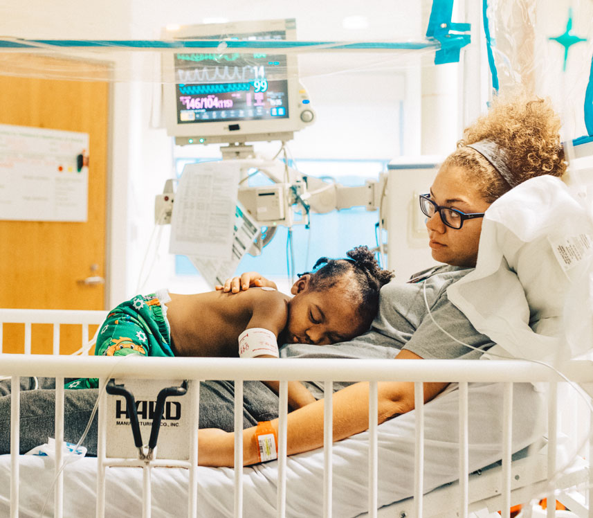 mother holding son in pediatric hospital bed