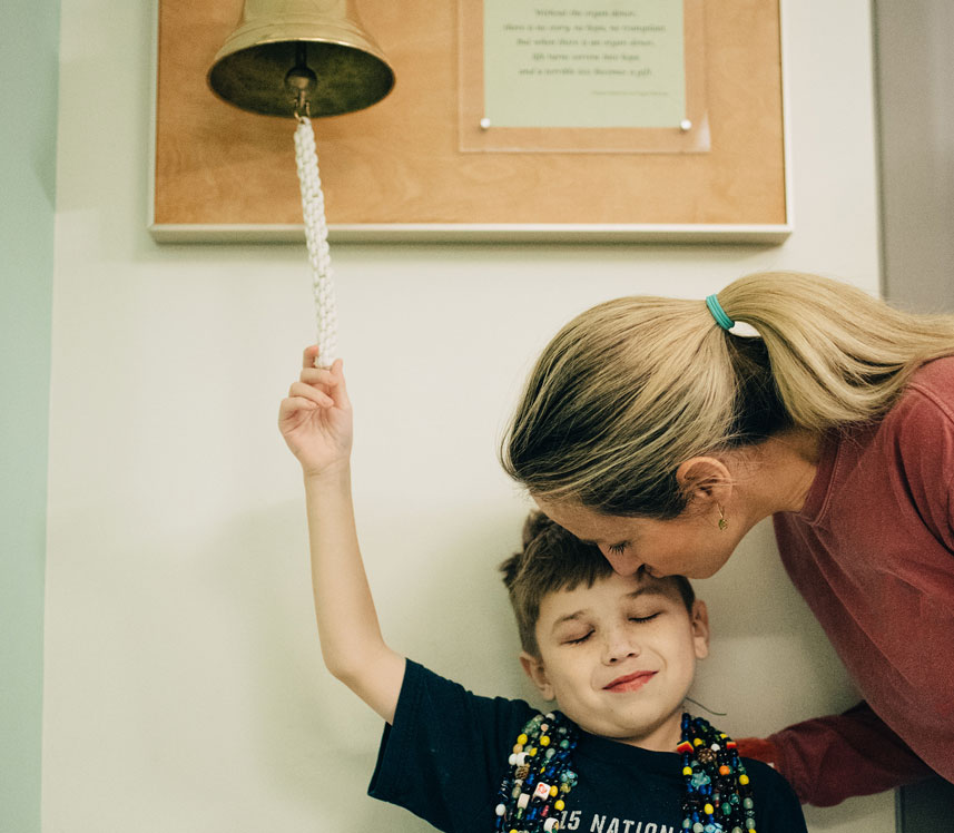 Young boy ringing bell at pediatric hospital marking the end of cancer treatment