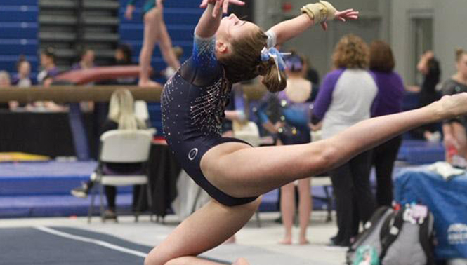 Carson, a teen athlete, competes in floor exercise at local gymnastics competition