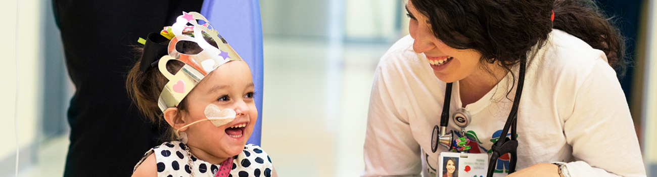 little girl wearing a crown laughing with a nurse in a hospital hallway