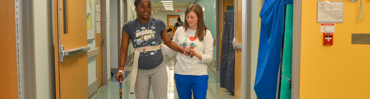 Girl walking with assistance of therapist down a hallway in Inpatient Rehab after a brain injury.