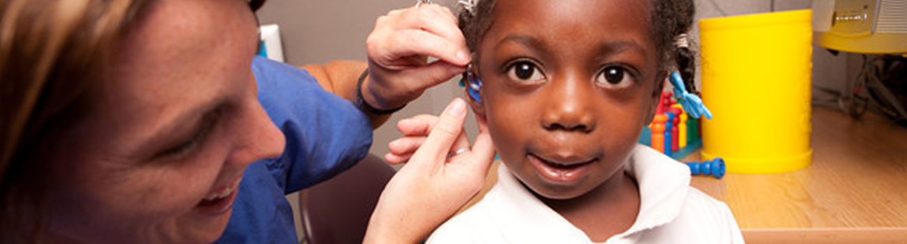 Audiologist adjusting young girl's cochlear implant at an outpatient rehabilitation appointment.