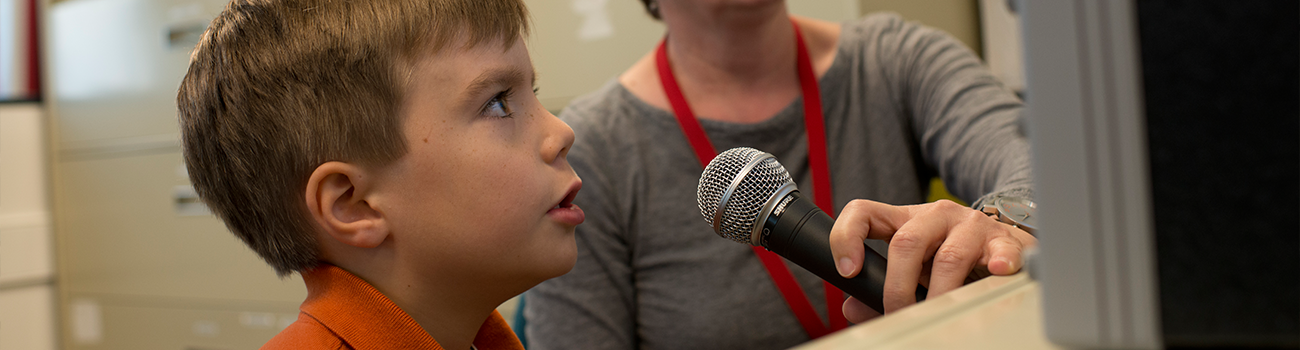 Young boy speaking into a microphone during a speech language pathology appointment.