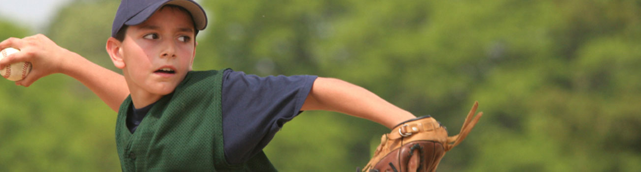 An adolescent boy throws a baseball intently.