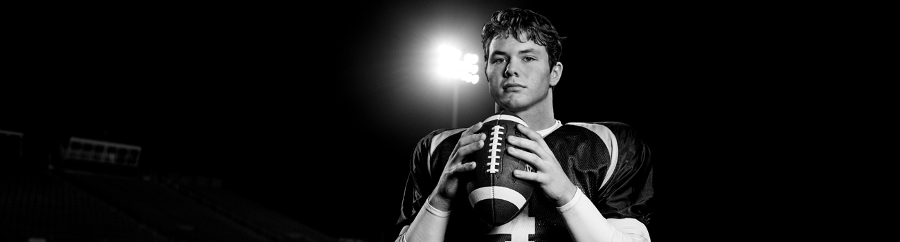 Teen athlete holding football after sports surgery and sports physical therapy