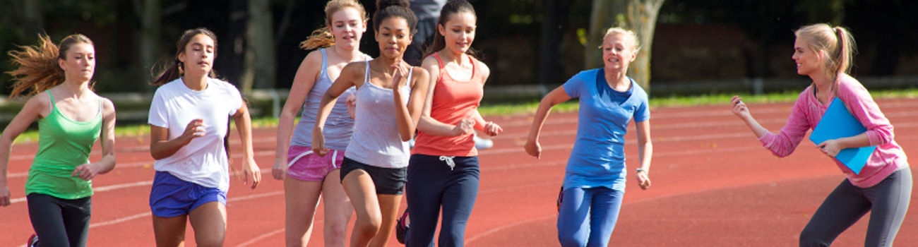 A team of adolescent girls race around the track while their coach times them at practice.