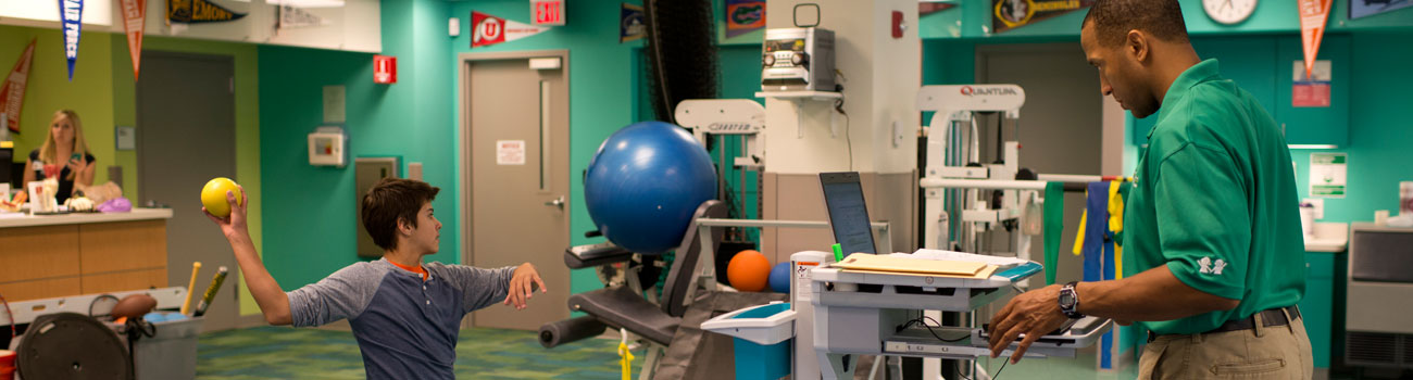 A young boy practices throwing a ball while a pediatric physical therapist evaluates his mechanics using Dartfish motion analysis technology.