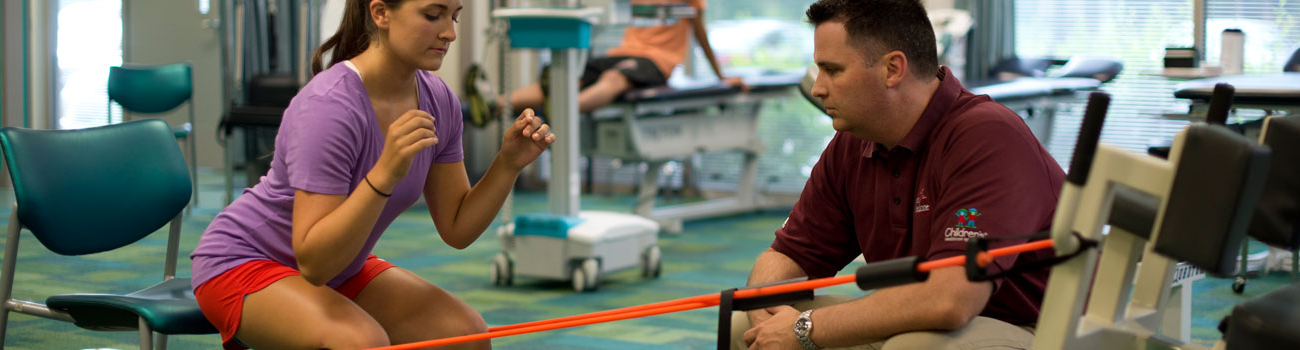 A teenage girl doing squat exercises in the physical therapy clinic while a pediatric-trained therapists monitors her form and progress.