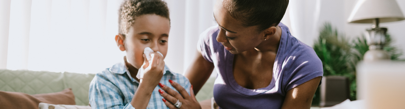 boy sneezing at home too sick for school