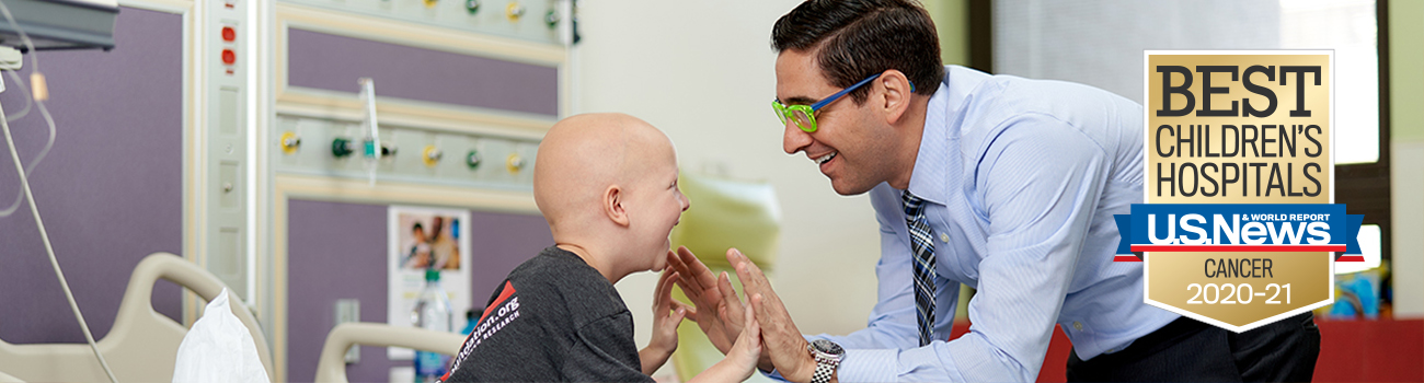 bald cancer patient high fives doctor