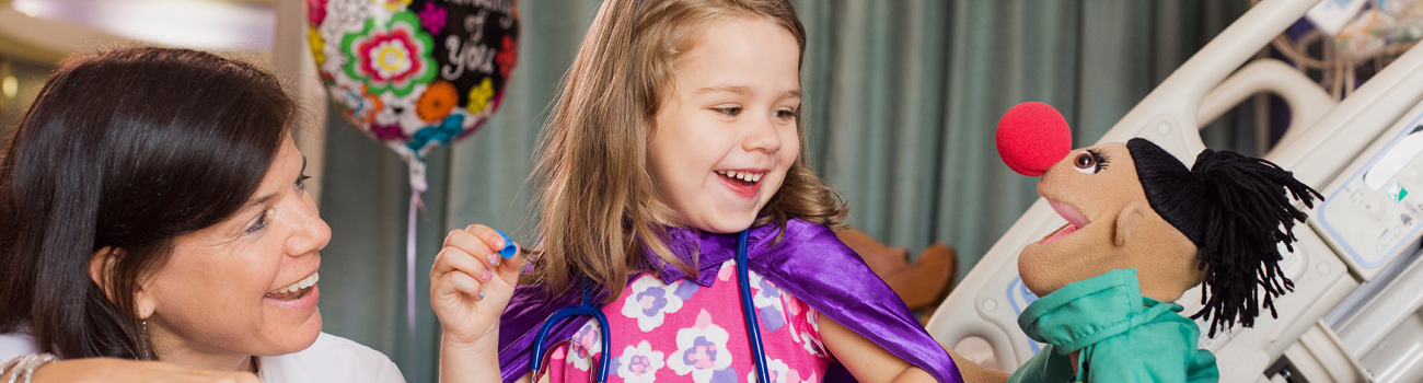 little girl in purple cape laughing with puppet