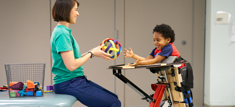 Inpatient rehab child playing with ball with nurse